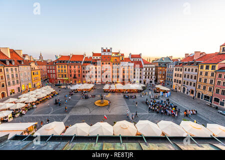 Warsaw, Poland - August 22, 2018: Historic cityscape with high angle view of colorful architecture rooftop buildings in old town market square at nigh - Stock Photo