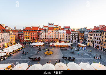 Warsaw, Poland - August 22, 2018: Historic cityscape with high angle view of colorful architecture rooftop buildings and horse carriage tour in old to - Stock Photo