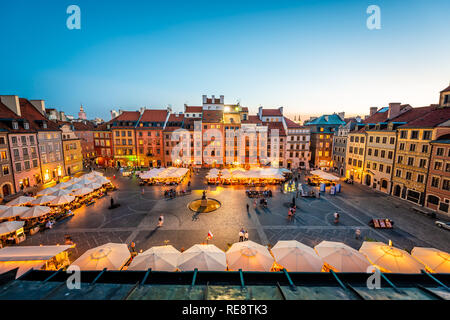Warsaw, Poland - August 22, 2018: Historic cityscape with high angle view of colorful architecture rooftop buildings and flag in old town market squar - Stock Photo