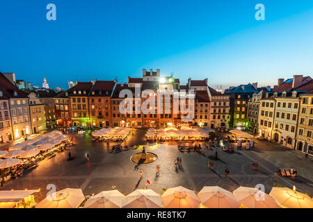 Warsaw, Poland - August 22, 2018: Cityscape with high angle view of architecture rooftop buildings and dark sky in old town market square at night - Stock Photo