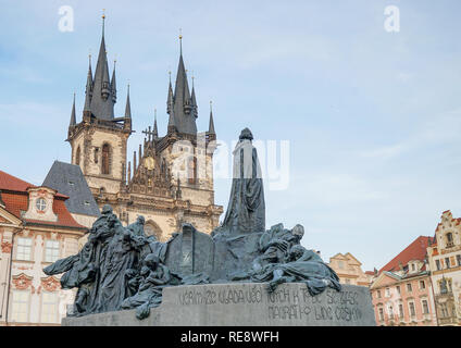 Jan Hus Monument on Old Town Square in Prague with magnificent town houses and church - Stock Photo
