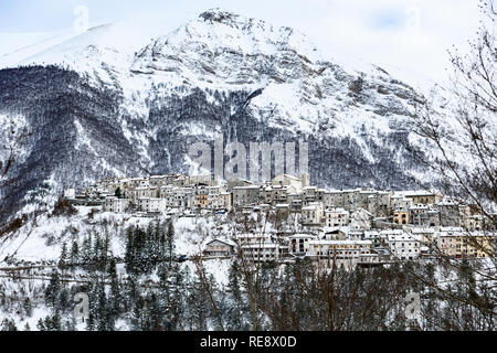 Aerial view of the beautiful snow-covered village of Opi with snow-capped mountains in the background. - Stock Photo