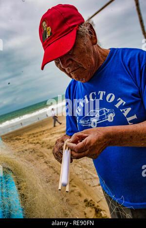 San Pedro, Ecuador - September 14, 2018 - fishing nets being repaired by fishermen - Stock Photo