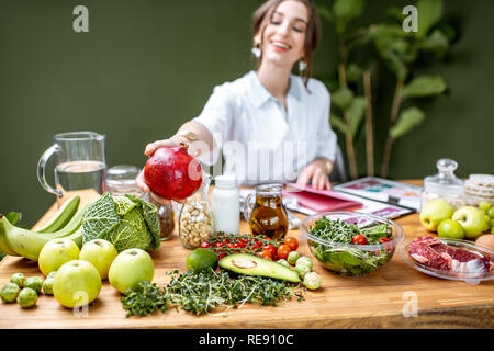 Woman dietitian in medical uniform working on a diet plan sitting with different healthy food ingredients in the green office - Stock Photo