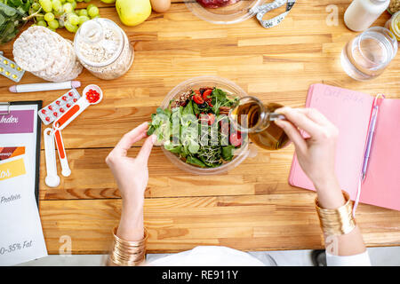 Dietitian working on a healthy diet pouring olive oil into the salad at the table full of various healthy products, view from above - Stock Photo
