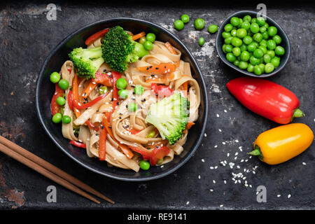 Asian stir fry with udon noodles and vegetables. Broccoli, green pea, pepper, carrots and pasta in black bowl. Top view - Stock Photo