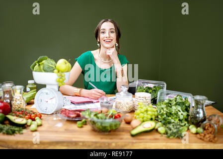 Beautiful woman dietitian working on a diet plan sitting with different healthy food ingredients in the green office - Stock Photo