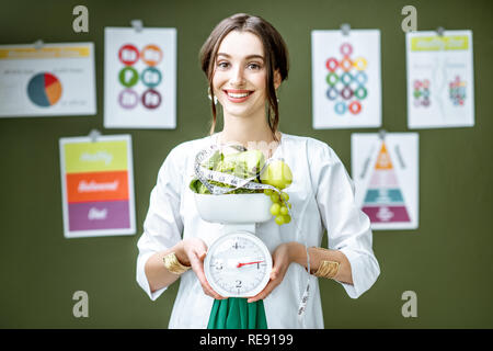 Young woman nutritionist in medical gown holding weights full of healthy products standing on the wall background with diet schemes - Stock Photo