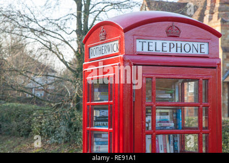 Traditional english red telephone box in a countryside village in Rotherwick, Hampshire. - Stock Photo
