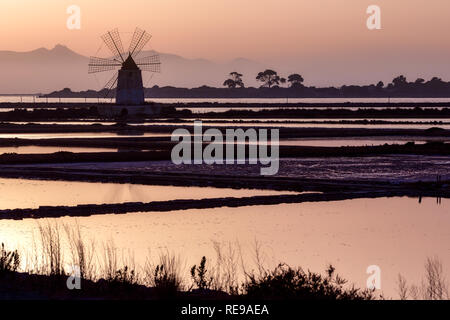 Sunset at the old salt works in the Laguna dello Stagnone near Trapani, Sicily, Italy - Stock Photo