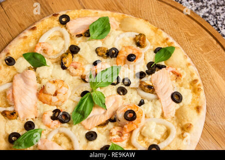Close Up pizza ingredients. Basil leaves on seafood pizza. - Stock Photo