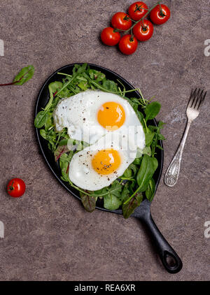 Two fried eggs on pan with different kinds of herbs, arugula, spinach, chard and cherry tomatoes, with fork on brown background, concept of a healthy  - Stock Photo