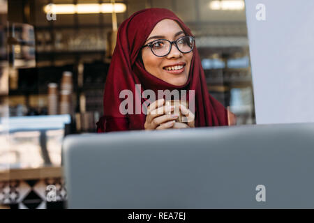 Pretty islamic girl in hijab and eyeglasses sitting at cafe with coffee in hand and looking away. Smiling muslim female at cafe with laptop. - Stock Photo