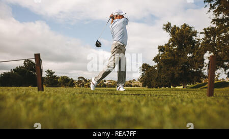 Professional golfer taking shot on the golf course. Senior golf player swinging golf club on the green. - Stock Photo