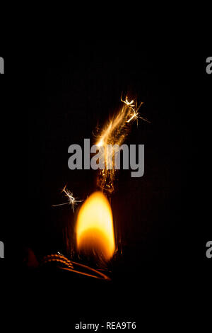 flame of fire from a gas lighter on a black background in the dark - Stock Photo