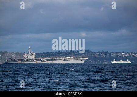 190120-N-EH218-0028 PORT BLAKELY, Wash. (Jan. 20, 2019) The Nimitz-class aircraft carrier USS Carl Vinson (CVN 70) sails past a Washington state ferry as it transits the Puget Sound on its way to Naval Base Kitsap-Bremerton. The Vinson is scheduled to change homeports to Bremerton while the Nimitz-class aircraft carrier USS John C. Stennis (CVN 74) undergoes its mid-life refueling overhaul in Newport News, Va. (U.S. Navy photo by Mass Communication Specialist 1st Class Ryan J. Batchelder/Released) - Stock Photo
