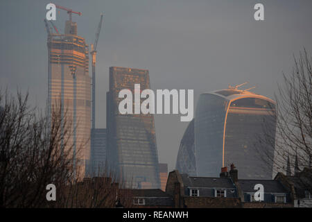 London, UK. 21st January, 2019. The rising sun shines on the tower blocks of the City of London. Credit: Guy Bell/Alamy Live News - Stock Photo