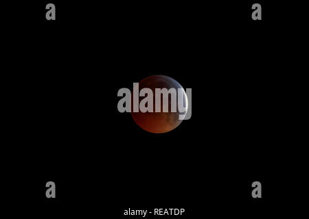 Woking, Surrey, England, UK, 21st January 2019.  The Super Blood Wolf Moon, the lunar eclipse of 21 January 2019, viewed from Woking, Surrey, south-east England, UK.  The shadow of the Earth partially covers the Moon shortly before totality of the eclipse. Credit: Graham Prentice/Alamy Live News. - Stock Photo