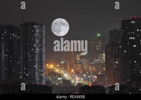 Nanjing, China. 21st Jan, 2019. The full moon rises over buildings in Nanjing, east China's Jiangsu Province. Credit: SIPA Asia/ZUMA Wire/Alamy Live News - Stock Photo