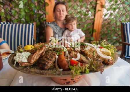 Rhodes, Greece. May 30, 2018. Meze plate with traditional local food on table in local restaurant in front of a family. Old Town, Island of Rhodes, Eu - Stock Photo