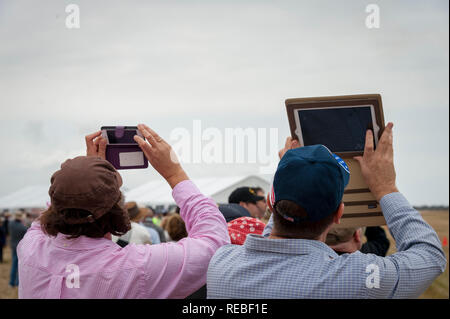Two airshow spectators taking photographs with their hand held devices - Stock Photo