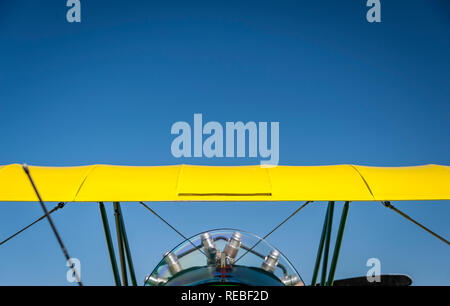 Vivid yellow top wing of a vintage biplane against a blue sky - Stock Photo