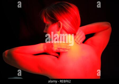 Young woman using a UV lamp, against a cold, tension, pain - Stock Photo