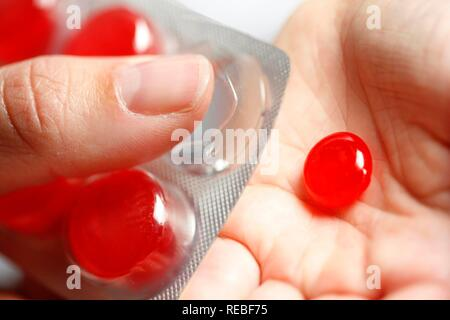 Throat lozenges being pressed out of a packet - Stock Photo
