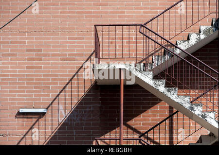 Concrete stairs with red metal railings against a red brick wall creating a strong diagonal shadow pattern - Stock Photo