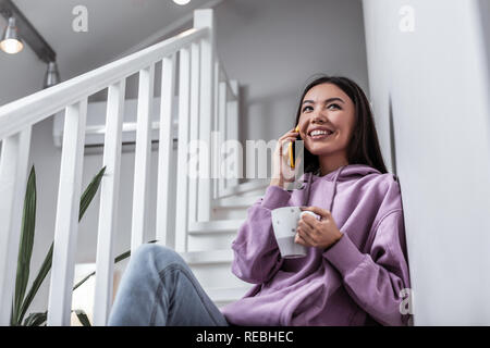 Cheerful young woman calling her boyfriend while drinking tea