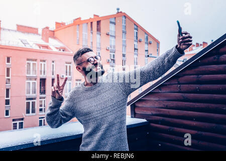 Cheerful bearded young man showing v sign - Stock Photo
