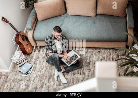 Positive cheerful man typing a text on his laptop - Stock Photo