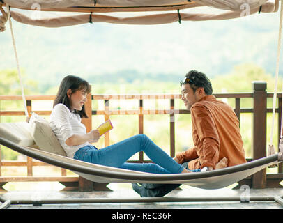 asian younger man and woman smiling face happiness emotion relaxing on cradle - Stock Photo