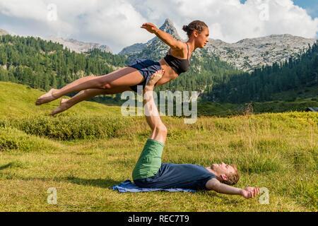 Young woman and young man doing acro yoga, mountain landscape, Berchtesgaden National Park, Berchtesgadener Land, Upper Bavaria - Stock Photo