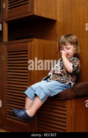 Two year old girl having a tantrum sitting on 'naughty chair - Stock Photo