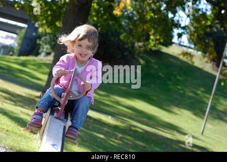 Two and a half year old girl having fun on the seesaw at a park - Stock Photo