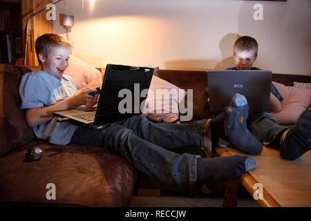 Brothers, 11 and 13 years old, with laptop computer in the living room, playing a car racing computer game on two computers - Stock Photo