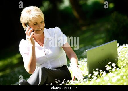 Woman wearing a ladies' suit, trouser suit, businesswoman, early 40s, working on her laptop in a park, on her mobile - Stock Photo