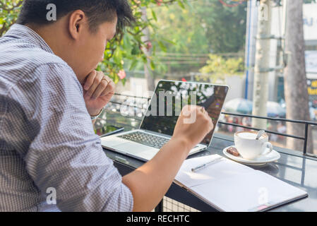 Asian investor watching the change of stock market on laptop - Stock Photo