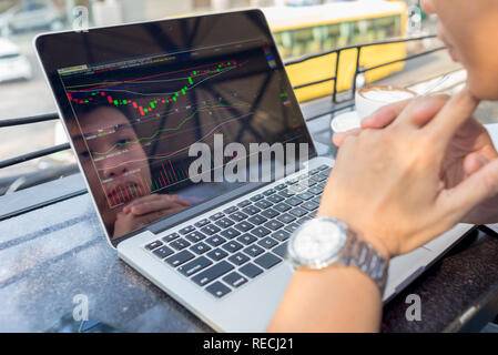 Young investor watching the change of stock market on laptop - Stock Photo