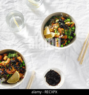 Two vegetarian poke bowl. Tofu, rice, seaweed, green peas and onions tasty and healthy vegetarian food. Top view flat lay - Stock Photo
