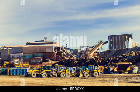 Wheel loaders and other mining machines parked next to the old mining buildings, with blue sky with clouds in the background - Stock Photo