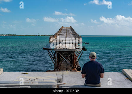 man flying a drone in damaged bridge in key west island florida highway panorama - Stock Photo
