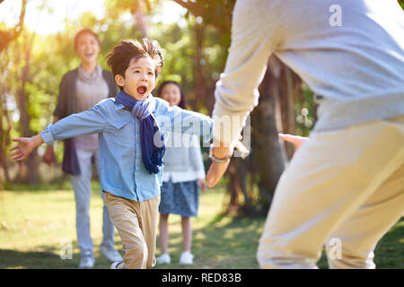 asian little boy son running towards father's embrace. - Stock Photo