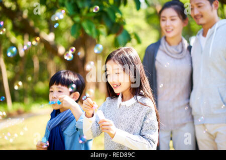 little asian kids boy and girl sister and brother blowing bubbles in a park with parents watching from behind. - Stock Photo