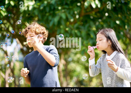 little asian girl and caucasian boy playing together blowing soap bubbles outdoors in a park. - Stock Photo