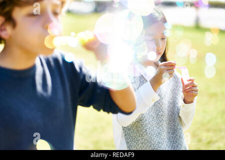 little asian girl and caucasian boy playing together blowing soap bubbles outdoors in a park.