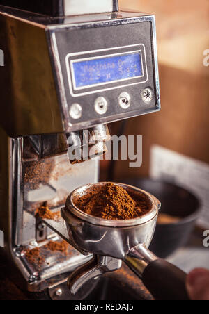Cropped image of barista using coffee grinder holding portafilter with ground coffee. - Stock Photo