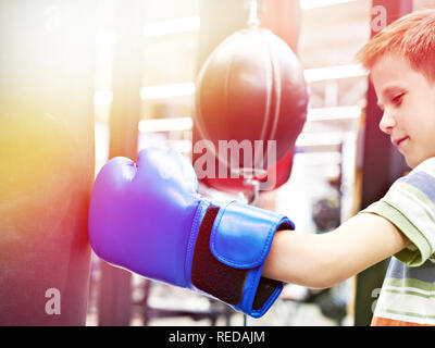 Boy in a boxing glove and punching bag - Stock Photo