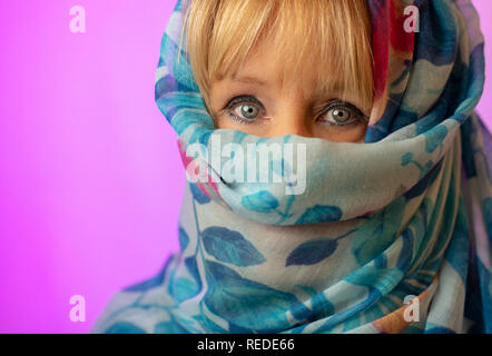 White woman with blond hair and blue eyes wearing a blue headscarf as a fashion accessory with only eyes and fringe showing against a pink background. - Stock Photo